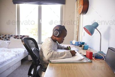 Young Boy In Bedroom Wearing Headphones And Doing Homework