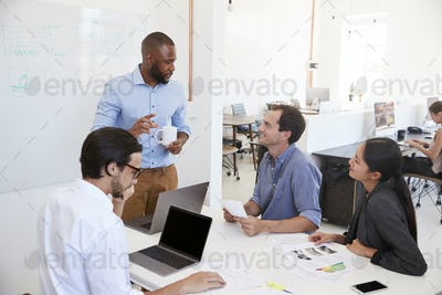 Young black man presenting an office meeting at a whiteboard