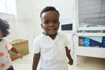 Portrait Of Smiling Young Boy Standing In Playroom