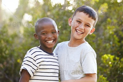 Portrait of two boys outdoors laughing and looking to camera
