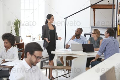 Woman talking to colleagues at a desk in open plan office