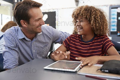 Teacher and schoolboy with tablet looking at each other