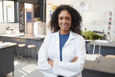 Female teacher in lab coat smiling in school science room