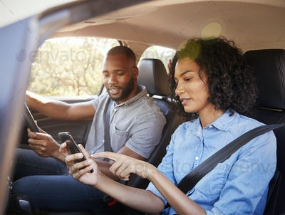 Young black couple navigating with smartphone on a road trip