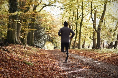 Rear View Of Mature Man Running Through Autumn Woodland