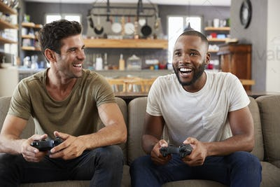 Two Male Friends Sitting On Sofa In Lounge Playing Video Game