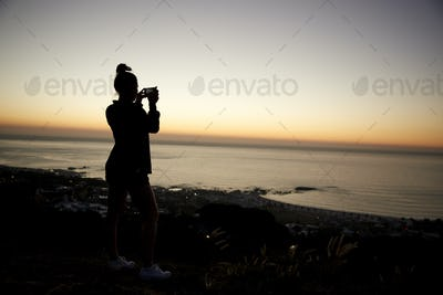 Girl taking photos with phone on beach, silhouette at sunset