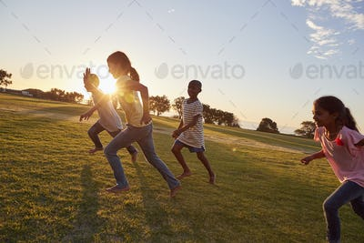 Four children running barefoot uphill in a park