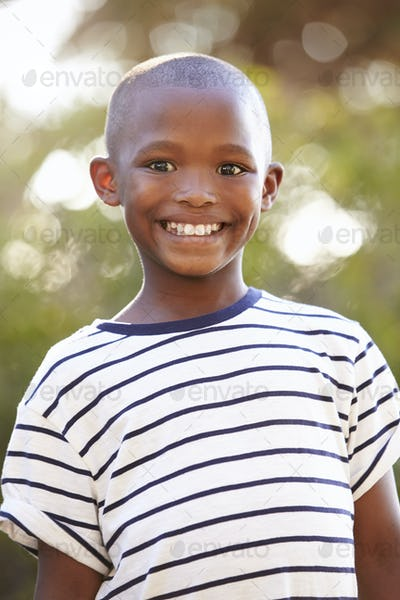Smiling young black boy looking away from camera outdoors