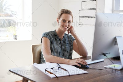 Smiling white woman working in an office looking to camera