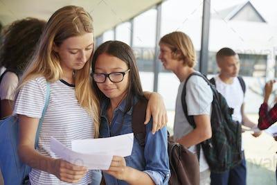 Two girls sharing exam results in school corridor
