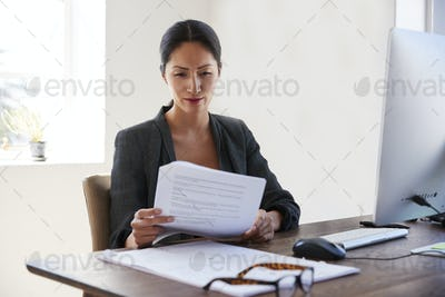 Young Asian woman reading documents at her desk in an office