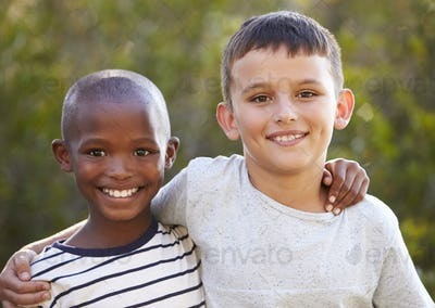 Two boys, arms around each other smiling to camera outdoors