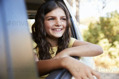 Young girl smiling and looking out of open car window