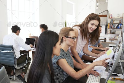 Three women working together at computer in open plan office
