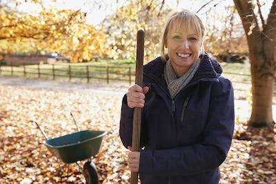 Portrait Of Mature Woman Raking Autumn Leaves In Garden
