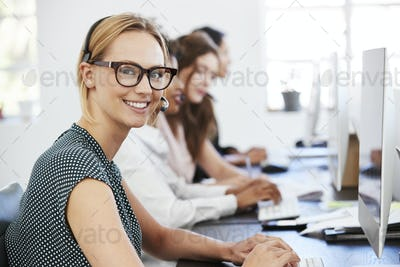 Young white woman with headset smiling to camera in office