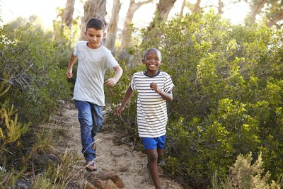 Two smiling young boys racing on a forest path
