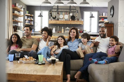 Two Families Sitting On Sofa Watching Television Together