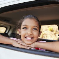 Young black girl looking up out of car window smiling