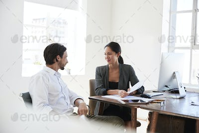 Man and woman discussing documents at a desk in an office