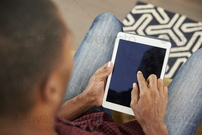 Man Sitting On Sofa At Home Looking At Digital Tablet
