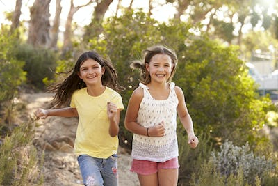 Two happy young girls running in a forest, close up