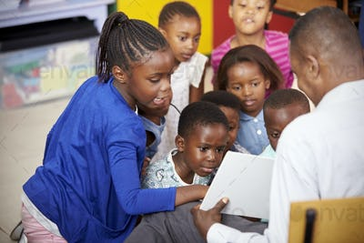 Teacher showing kids a book during elementary school lesson