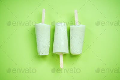 Green popsicles on green pastel background