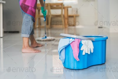 Young woman cleaning floor with mop and bucket