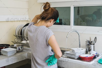 Tired young woman with gloves washing dishes