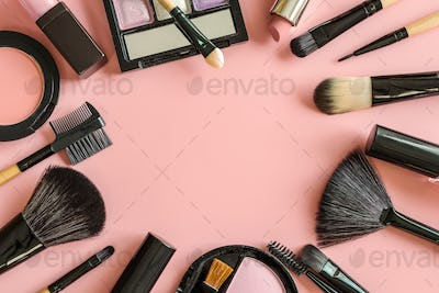 Set of make up brushes and cosmetics on pink background