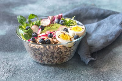 Bowl of wild rice with avocado, egg and lettuce