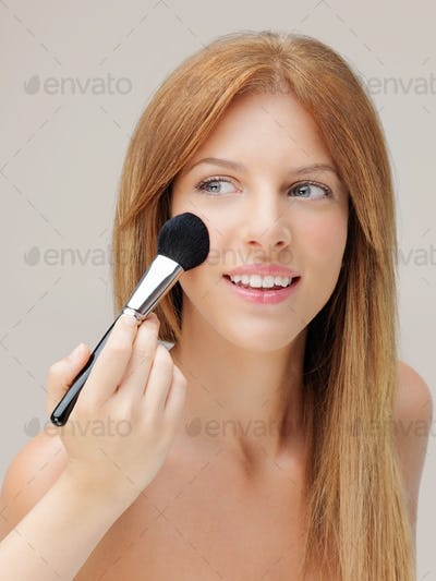happy woman applying blusher with brush