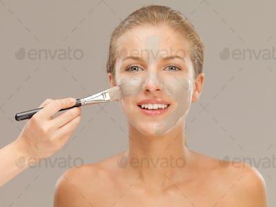beautiful woman applying mud mask with brush
