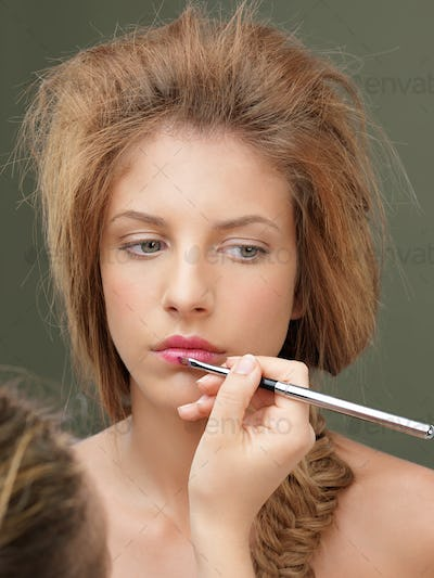 young woman applying pink lipstick with brush