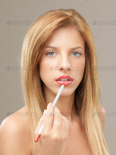 beautiful blonde woman applying lip liner