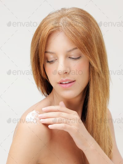 blonde woman applying body lotion on shoulder
