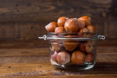 unpeeled hazelnuts in a glass jar, on rustic wood