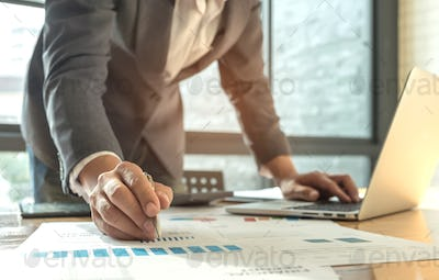 Men wearing suits are using a pen pointing on graph and another hand use laptop.