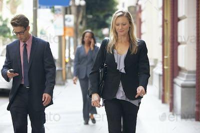 Group Of Businesspeople Walking Along Street