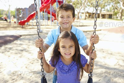 Boy And Girl Playing On Swing In Park