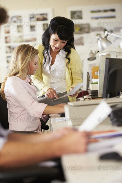 Two Women Working At Desks In Busy Creative Office