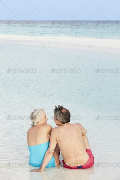 Rear View Of Senior Couple Sitting On Beautiful Beach