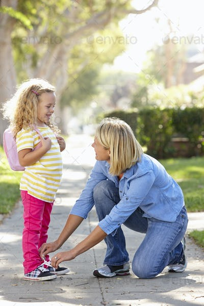 Mother Helping Daughter Tie Shoe Laces On Walk To School