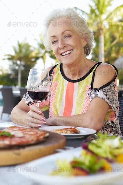 Senior Woman Enjoying Meal In Outdoor Restaurant