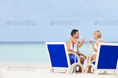 Couple On Beach Relaxing In Chairs And Drinking Champagne