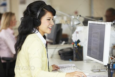 Woman With Headset Working At Desk In Busy Creative Office