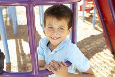 Boy On Climbing Frame In Park