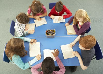 Overhead View Of Schoolchildren Working Together At Desk